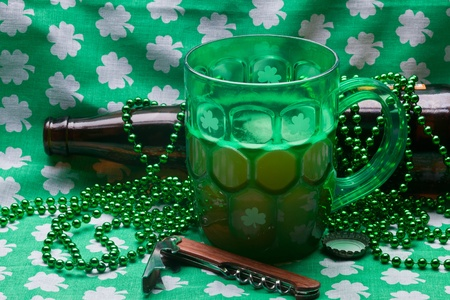 Beer mug, beads, bottle opener on a green material on wooden table. photo