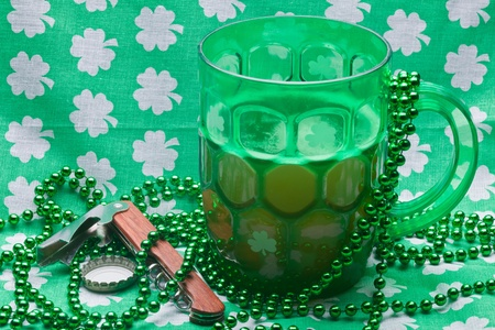 Beer mug, beads, bottle opener on a green material on wooden table. Stock Photo - 8898879