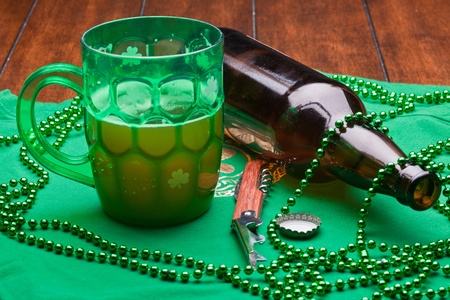 Beer mug, beads, bottle opener on a green material on wooden table. Stock Photo - 8898966