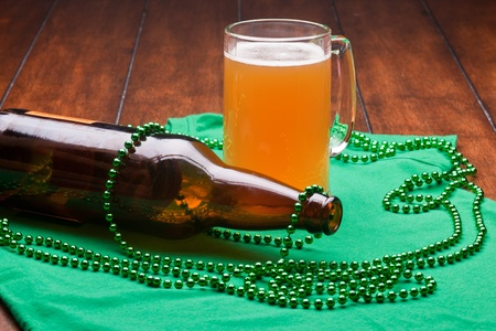 Beer mug, beads, bottle opener on a green material on wooden table. Stock Photo - 8958114