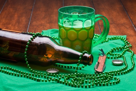 Beer mug, beads, bottle opener on a green material on wooden table. Stock Photo - 8958120