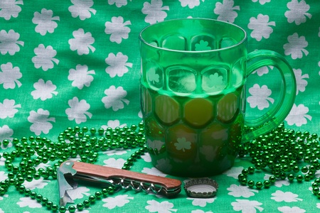 Beer mug, beads, bottle opener on a green material on wooden table. Stock Photo - 8958121
