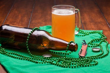 Beer mug, beads, bottle opener on a green material on wooden table. Stock Photo - 9225566