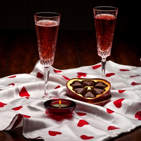 Champagne, heart shaped box of chocolate on a table