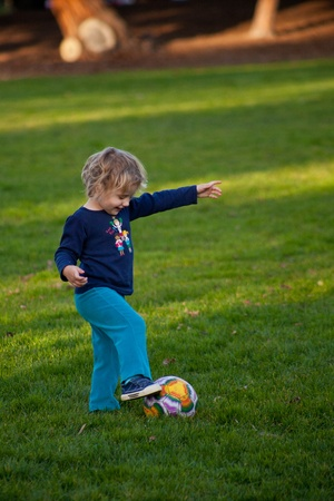 Cute little European girl having fun during soccer class in a park. Banco de Imagens