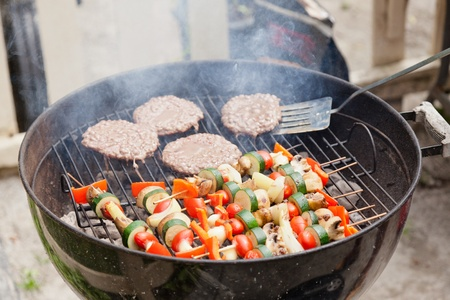 outdoor living: Food cooking on a charcoal grill in a park.