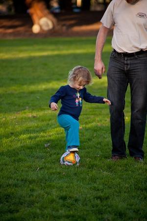 Cute little European girl having fun during soccer class in a park. photo