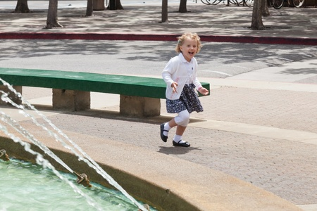 Having fun running around the fountain in the park. photo