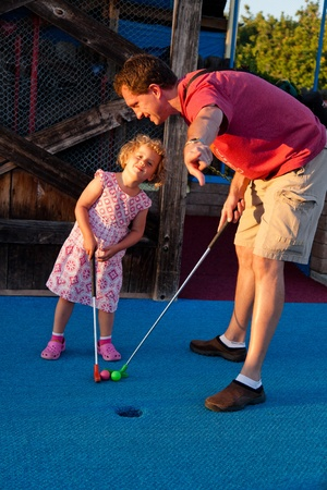 putt: Having fun at miniture gold site on sunny summer afternoon.