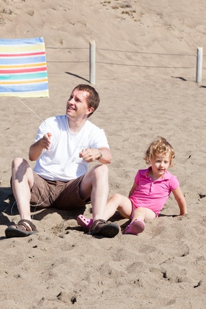 Father and daughter flying kite on the beach on sunny day. photo