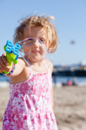 Having fun with bubbles  on a beach on sunny day. photo