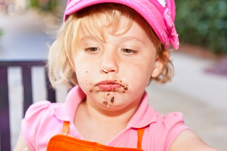 Eating a delicious chocolate cupcake with chocolate frosting. Stock Photo - 13040828