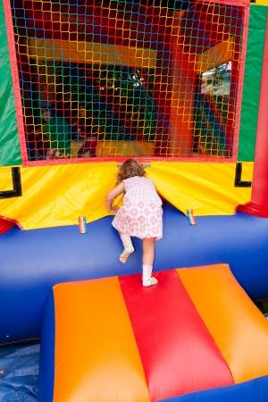 Plezier hebben in opblaasbare springen huis tijdens verjaardagsfeestje. Stockfoto
