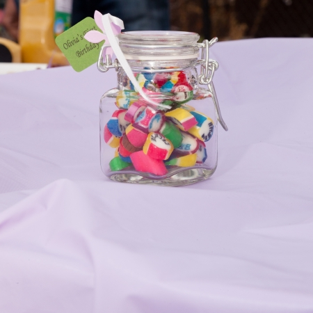 Jar with assorted candies as a gift to participant of 1st bistday party. photo
