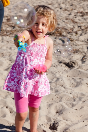 Having fun with bubbles  on a beach on sunny day.