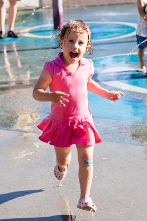 playground children: Divertirse con el agua en el patio de recreo en el parque Foto de archivo