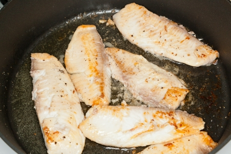 Frying tilapia filets on a large non-stick frying pan. photo