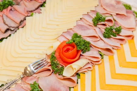 Party tray of assorted meats and cheeses with  flower made of tomato in the middle.