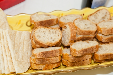 Basket full of various bread slices on a table. photo