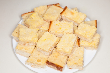 lemony: Lemon squares, a popular bar cookie dessert made with a cookie crust and lemony topping