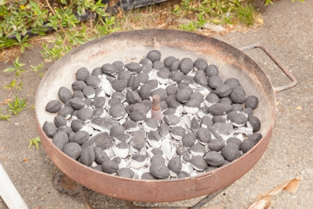 Brazier grill loaded with burning charcoal briquettes.