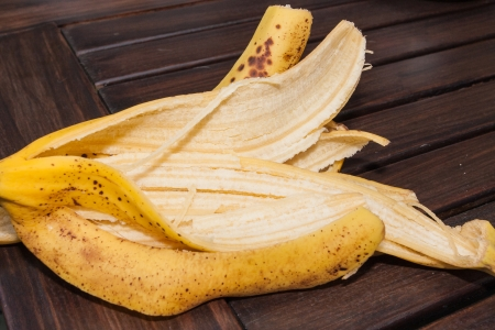 Banana peel on dark brown wooden table. photo