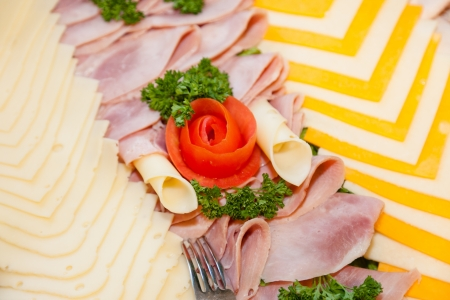 Party tray of assorted meats and cheeses with  flower made of tomato in the middle. photo
