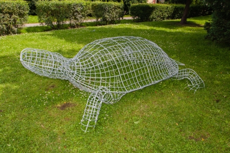 Shaped wire cage used to develop and maintain clearly defined shapes of live perennial plants.