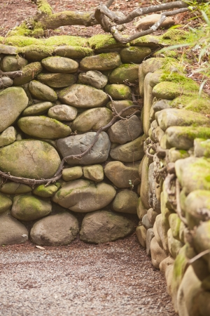 Wall made of stones in traditional Japanese garden.