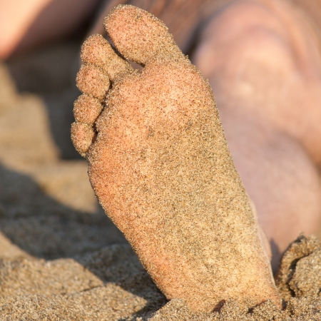 dirty feet: Foot covered with wet sand on the beach.