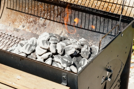 briquettes: Brazier grill loaded with burning charcoal briquettes.