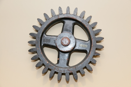 Old black wooden cogwheel as a decoration on a wall. photo