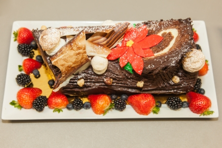 Beautifully decorated delicious chocolate layered roll. on rectangle plate. photo