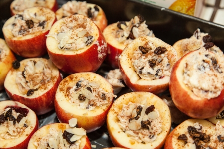 Tray of baked stuffed apples with cranberries and walnuts sprincled with cinammon