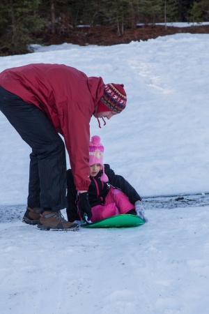 Having fun sledding down hill in the snow. photo