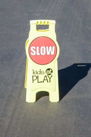 take down notice: Plastic portable slow down children at play sign.