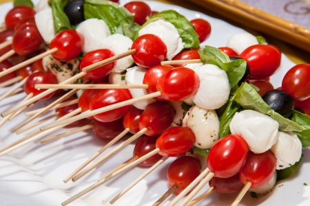 Tomato skewers piled high on a platter, dressed up with a little basil oil.b Imagens