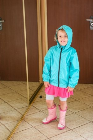 Wearing blue raincoat and pink rubber boots. photo