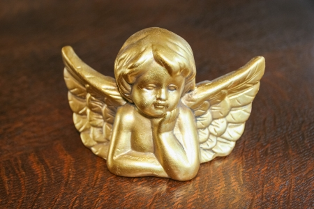 statuette: Decorative Christmas angel head figurine on a table.