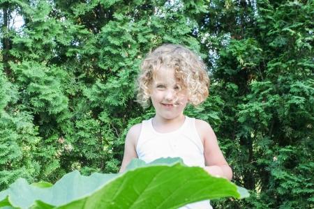 Cute little girl walking in the summer garden.