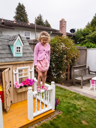 Having fun jumping down from playhouse fense in a garden.