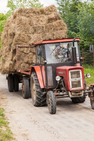 Tractor with large loads of baled hay on a village road. photo