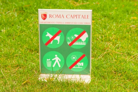Sign prohibiting walking on grass, picking flowers ant littering. photo