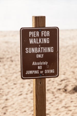 Warning sign on a pier prohibiting jumping and diving. photo