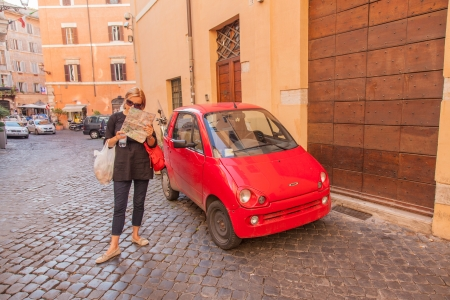 Red microcar on a street of Rome, Italy. Stock Photo
