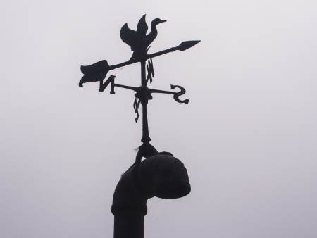 Weathercock is an instrument for showing the direction of the wind. They are typically used as an architectural ornament to the highest point of a building. Stock Photo