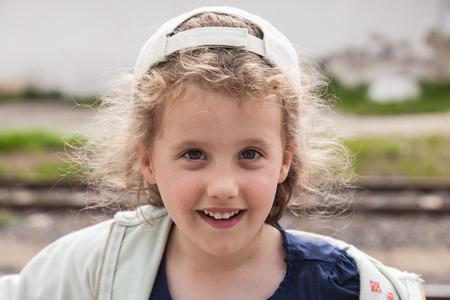 Cute little caucasian girl in a baseball hat.
