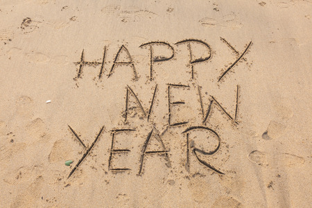 Happy New Year written in the sand of a beach photo