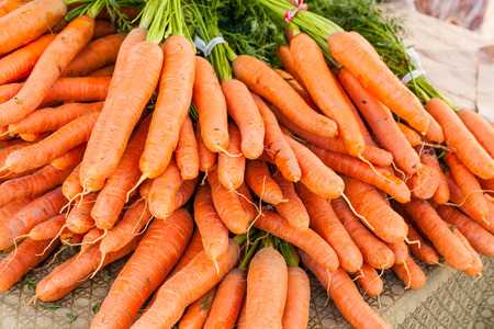 Bunches of fresh carrots for sale at local farmers market. Imagens