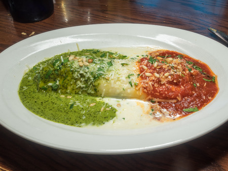 The grilled chicken, veggie and ricotta filled cannelloni is topped with three sauces: marinara (red), alfredo (white) and pesto (green) in a tribute to the colors of the Italian flag. photo